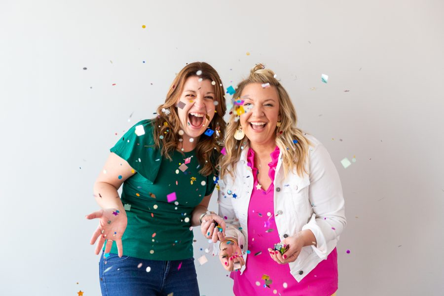 Two women laughing and throwing confetti