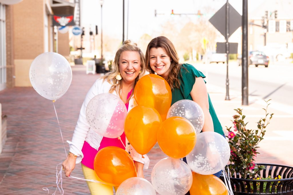 two women holding balloons and smiling